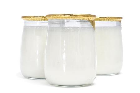 yogurt natural: algunos yogures en tarro de cristal sobre un fondo blanco Foto de archivo