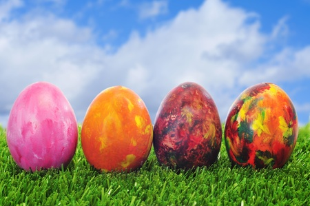 some easter eggs of different colors on the grass photo
