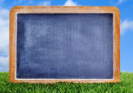 scores: a blank blackboard on the grass to insert such as soccer matches or scores Stock Photo