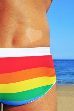 bathing man: someone wearing a rainbow swimsuit on the beach with a heart-shaped tan mark