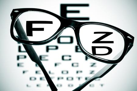 eyeglasses over a blurry eye chart Stock Photo - 12553842