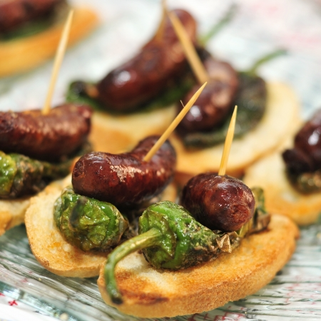 closeup of a plate with spanish pinchos made with chorizos an Padron peppers Stock Photo