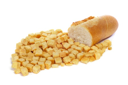 a pile of croutons and a piece of bread on a white background