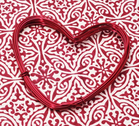 heart-shaped wire roll on a patterned background Stock Photo - 12893840