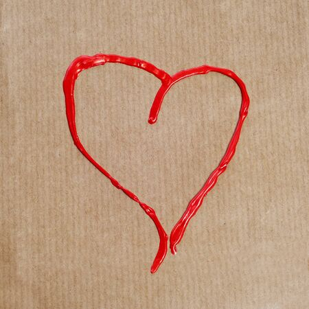 a heart drawn with red paint on a brown paper photo