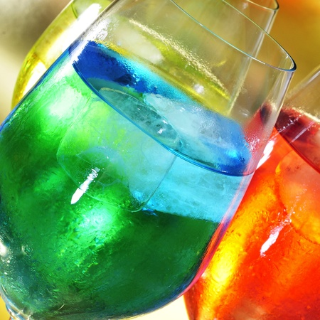thirstiness: some glasses with cocktails of different colors in a club