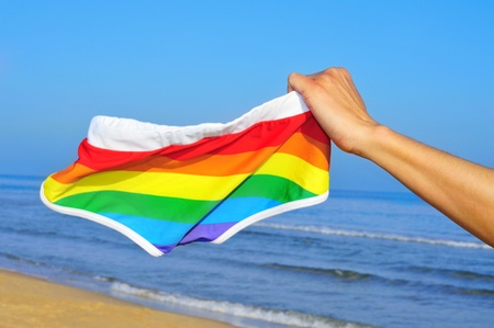 someone showing a rainbow swimsuit on the beach Stock Photo