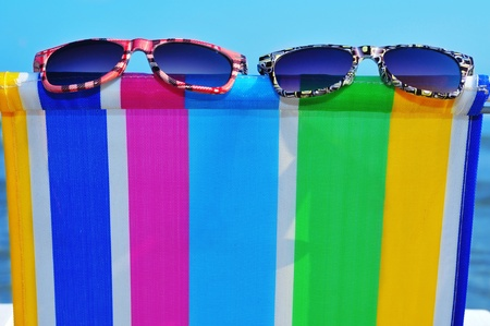 two pairs of sunglasses on a colorful deckchair on the beach Stock Photo - 12971287