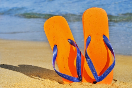 a pair of flip-flops on the sand of a beach photo