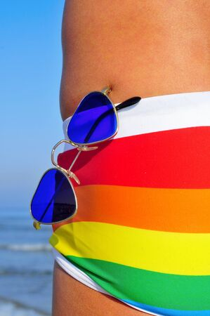 chilling out: someone wearing a rainbow swimsuit and heart-shaped sunglasses on the beach