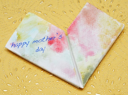 happy mothers day written in a paper folded heart Stock Photo