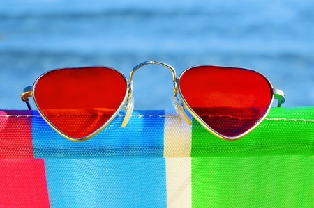 heart-shaped sunglasses on a colorful deckchair on the beach Stock Photo - 13232969