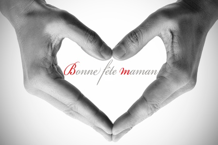 fete: hands forming a heart and the sentence bonne fete maman, happy mothers day in french Stock Photo