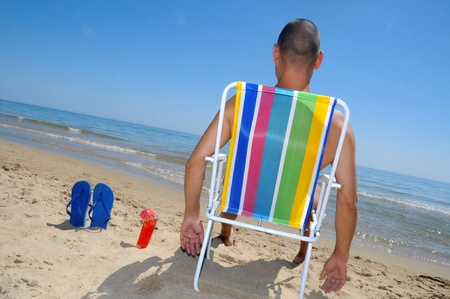 chilling out: a man chilling out with a cocktail on the beach Stock Photo