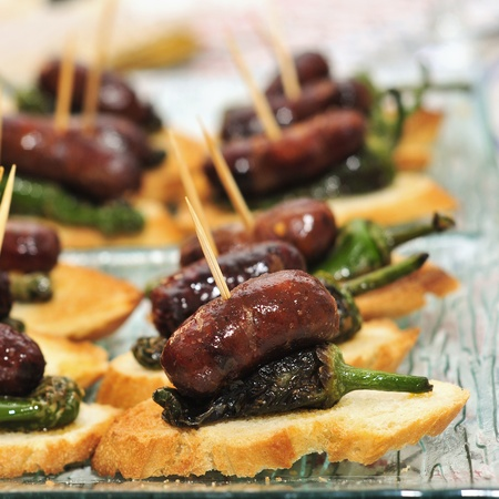 chorizos: closeup of a plate with spanish pinchos made with chorizos an Padron peppers Stock Photo