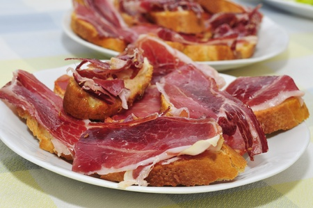slices of bread with spanish serrano ham served as tapas Stock Photo - 13332493