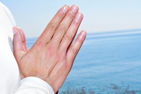 namaste: una persona meditando en la playa con sus manos en oraci�n mudra