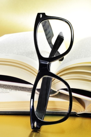 a pile of books and glasses symbolizing the concept of reading habit or studying Stock Photo - 13424360