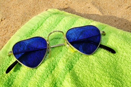 chilling out: heart-shaped sunglasses on a towel on the sand of a beach