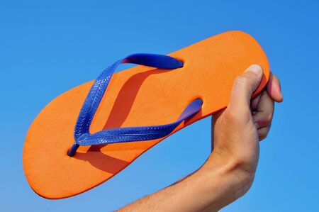 someone holding an orange flip-flops over the blue sky photo