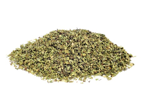 rich flavor: a pile of dried oregano on a white background Stock Photo