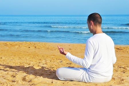 yogi man dressed in white meditating on the beach Stock Photo - 13486813