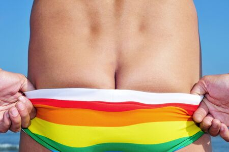 nudism: someone getting of his rainbow swimsuit on the beach Stock Photo