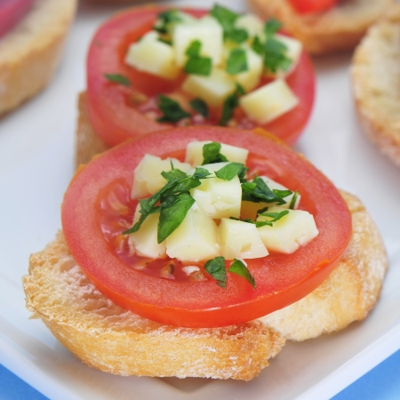 entree: closeup of some slices of bread topped with tomato and cheese