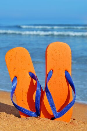 flip flops: a pair of orange flip-flops on the sand of a beach