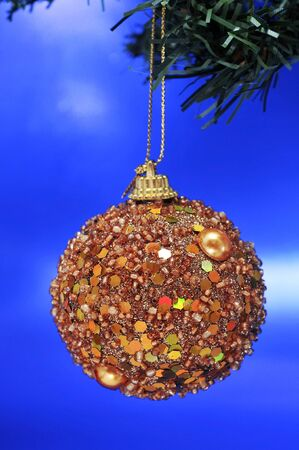 a shiny golden christmas ball hanging on a branch of a christmas tree photo