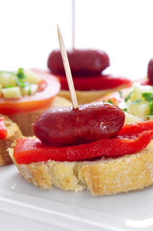 toothpick: closeup of a plate with spanish pinchos made with chorizos an red pepper Stock Photo