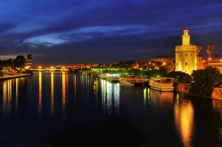 A view of the Guadalquivir River and the Torre del Oro, in Seville, Spain at night