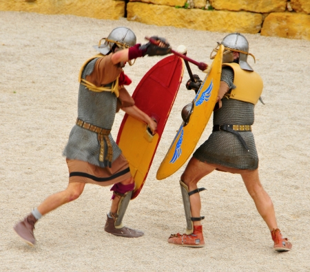 fight arena: Tarragona, Spain - May 26, 2012: Gladiators on the arena of Roman Amphitheater in Tarragona, Spain. Every year, the historic recreation program TarracoViva recreates a gladiators fight