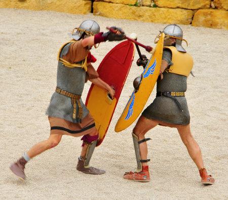 roman amphitheater: Tarragona, Spain - May 26, 2012: Gladiators on the arena of Roman Amphitheater in Tarragona, Spain. Every year, the historic recreation program TarracoViva recreates a gladiators fight