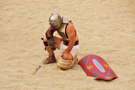 fight arena: Tarragona, Spain - May 26, 2012: A gladiator on the arena of Roman Amphitheater in Tarragona, Spain. Every year, the historic recreation program TarracoViva recreates a gladiators fight