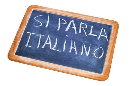 spoken: sentence si parla italiano, italian is spoken, written on a chalkboard