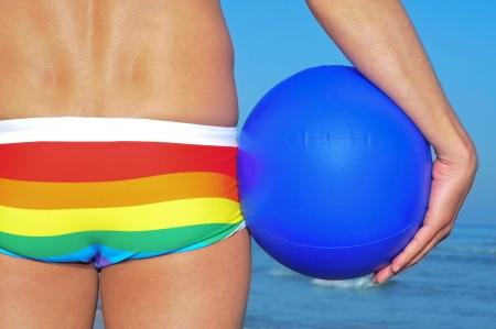 hombres gays: alguien que lleva un traje de baño del arco iris en la playa sosteniendo una pelota de playa