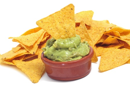 guacamole: a pile of nachos and a bowl with guacamole on a white background