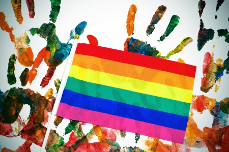transgender: a rainbow flag on a background with handprints of differents colors Stock Photo