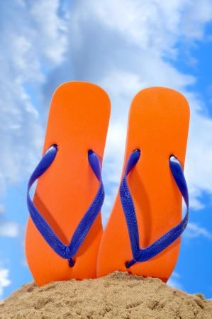 flops: a pair of orange flip-flops on the sand over the blue sky