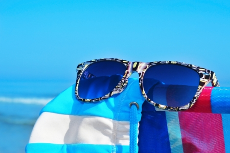 sunglasses and swimsuit on a colorful deckchair on the beach Stock Photo - 13987382