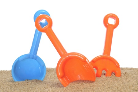 some beach shovels and rake on the sand on a white background photo
