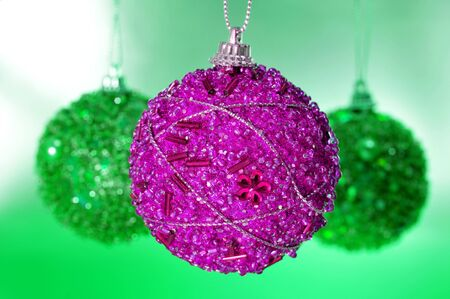 pink and green christmas balls hanging from a christmas tree photo