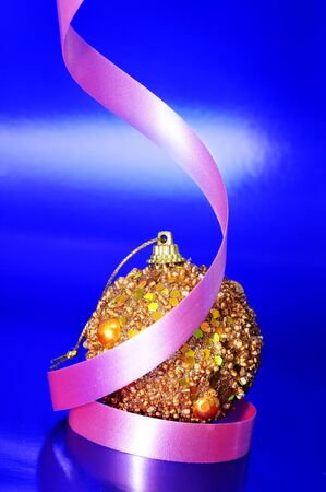 a shiny golden christmas ball with a pink ribbon on a blue background photo