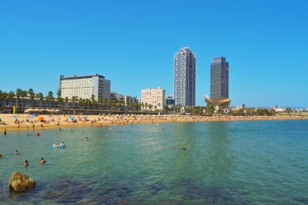 Barcelona, Spain - August 16, 2011: Barceloneta Beach with Hotel Arts and Mapfre Tower in the background in Barcelona, Spain. Arts is a 44-story hotel and its twin, an office building