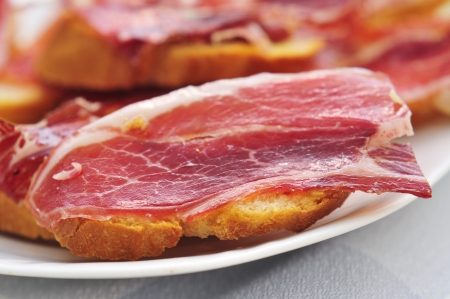 slices of bread with spanish serrano ham served as tapas photo