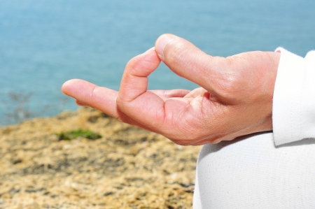 someone meditating on the beach with his hands in gyan mudra photo