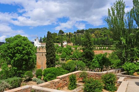 Granada, Spain - May 19, 2012: Gardens of La Alhambra with the Generalife in the background in Granada, Spain. La Alhambra is UNESCO World Heritage Site since 1984
