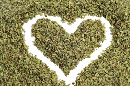 a heart drawn in dried oregano on a white background photo