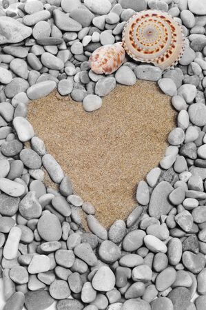 a heart made with pebbles on a shingle beach photo
